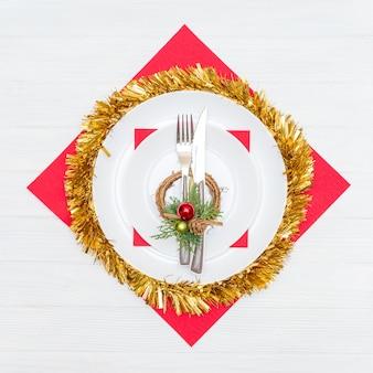 Nóż i widelec w białym talerzu na czerwonej serwetce ozdobiony świątecznym wieńcem na białym stole