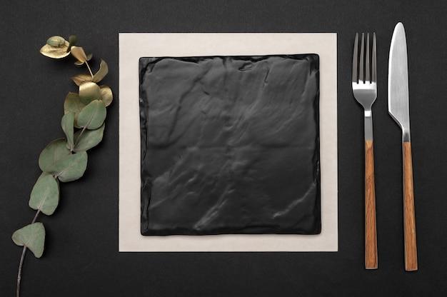 Nóż i widelec z kwadratową czarną tablicą łupkową dla tekstu menu lub przepisu i złotą gałąź eukaliptusa na czarnym stole