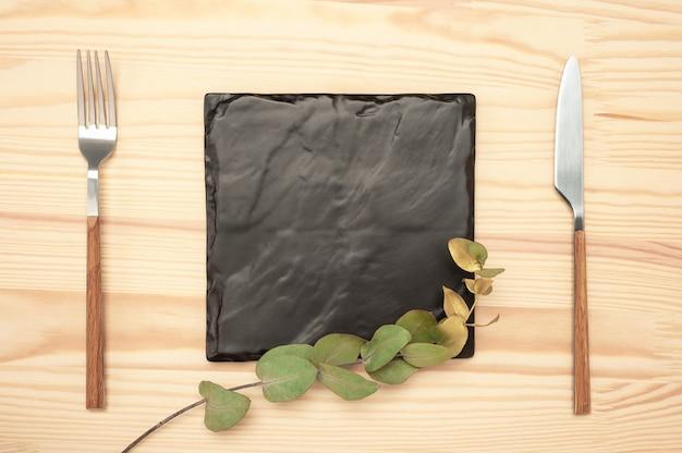 Nóż i widelec z kwadratową czarną tablicą łupkową dla tekstu menu lub przepisu i złotą gałąź eukaliptusa na drewnianym stole