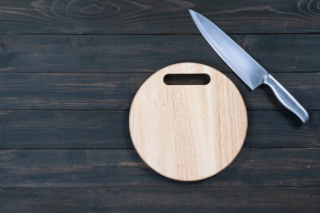 Nóż kuchenny i drewniana okrągła pusta deska do krojenia na drewnianym stole z bliska