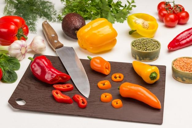 Nóż kuchenny i plasterki posiekanej papryki na desce do krojenia. soczewica, fasola mung i warzywa na stole. białe tło. widok z góry