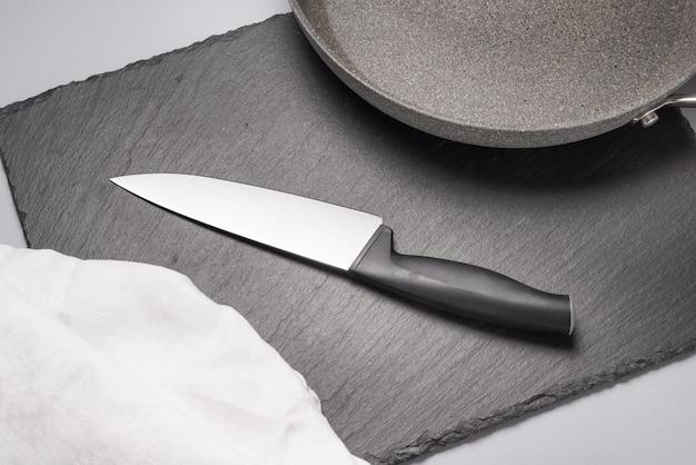 Nóż kuchenny z plastikową rączką na stole.