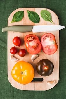 Nóż leży w pobliżu szpinaku i pomidorów
