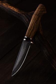 Nóż myśliwski ze stali damasceńskiej na drewnianym tle