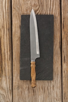 Nóż na czarnej płycie łupkowej