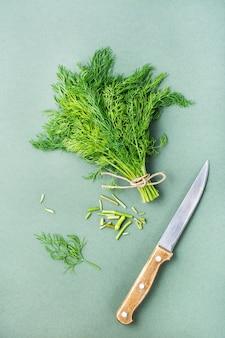 Nóż odcina łodygi z pęczka świeżego koperku na zielonym tle. zieloni witaminowe w zdrowej diecie. widok z góry i z pionu