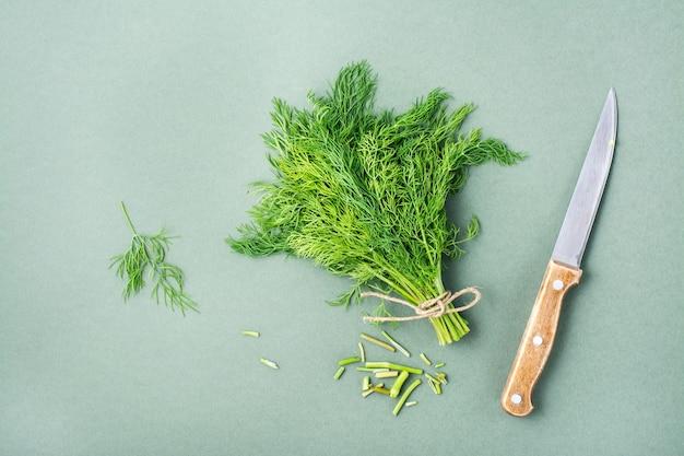Nóż odcina łodygi z pęczka świeżego koperku na zielonym tle. zieloni witaminowe w zdrowej diecie. widok z góry