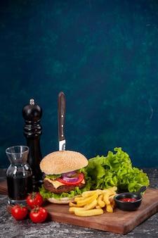 Nóż w kanapce z mięsem i frytkami pomidorami z zielonym pęczkiem łodygi na drewnianej desce ketchup z sosem na ciemnoniebieskiej powierzchni