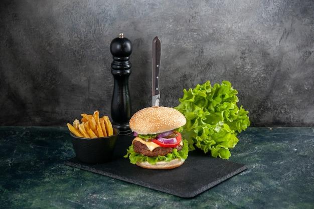 Nóż w kanapce z mięsem i zielonymi frytkami na czarnej tacy na szarej powierzchni