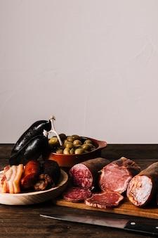 Nóż w pobliżu kiełbasy i oliwki