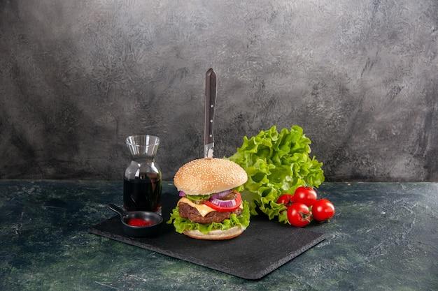 Nóż w pysznej kanapce z mięsem i zielonym pieprzem na czarnej tacy, pomidory z sosem ketchup z łodygą na szarej powierzchni