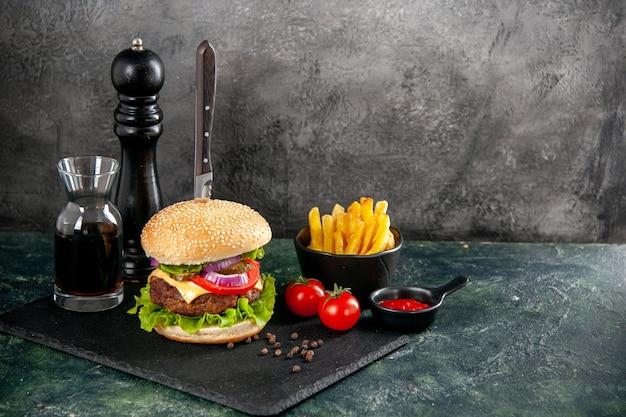Nóż w pysznej kanapce z mięsem i zielonym pieprzem na czarnej tacy, pomidory z sosem ketchupowym z frytkami z łodygi po prawej stronie na izolowanej ciemnej powierzchni