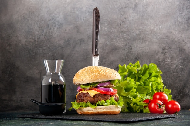 Nóż w pysznej kanapce z mięsem i zielonym pieprzem na czarnej tacy z pomidorami z sosem z łodygą na szarej powierzchni