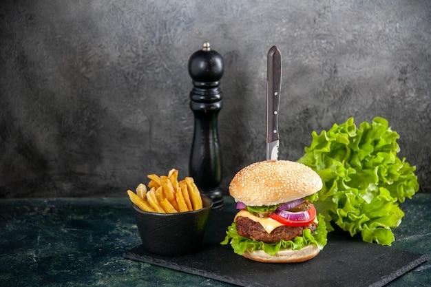 Nóż w pysznej kanapce z mięsem i zielonym pieprzem z frytkami po lewej stronie na czarnej tacy na szarej powierzchni