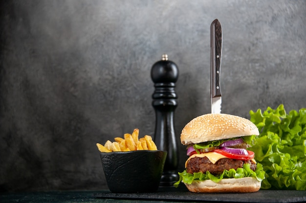 Nóż w pysznej kanapce z mięsem i zielonymi frytkami po lewej stronie na czarnej tacy na szarej powierzchni