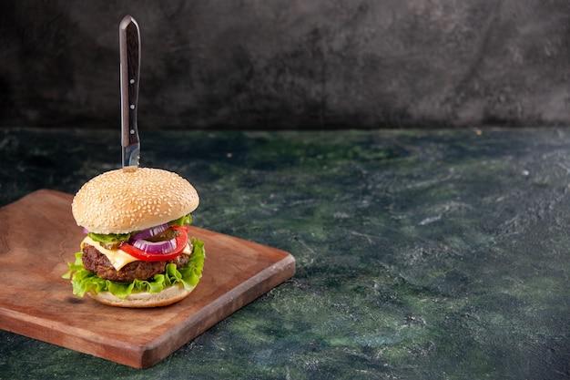 Nóż w smacznej kanapce mięsnej na drewnianej desce do krojenia po prawej stronie na izolowanej ciemnej powierzchni z wolną przestrzenią
