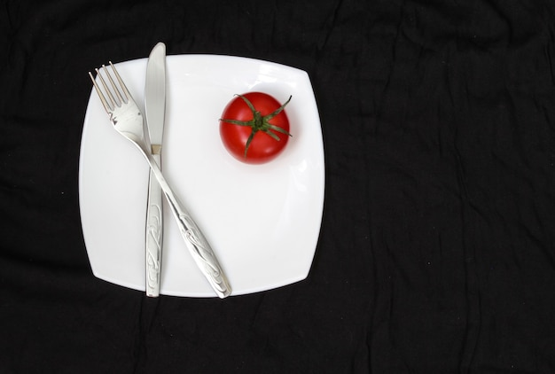 Nóż widelec i biały talerz z pomidorami na czarnym tle wyczyść talerz i sztućce na tle
