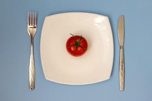 Nóż widelec i biały talerz z pomidorami na niebieskim tle wyczyść talerz i sztućce