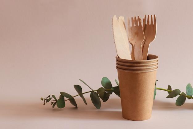 Noże, widelce i papierowe kubki z bliska. pojęcie zero waste i recycling.