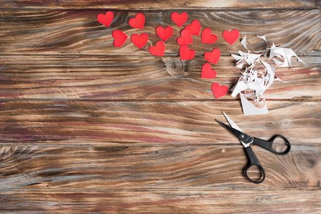 Nożyce i serca na tarcicy tle