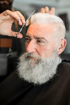 Nożycowy włosy starszy klient w zakładzie fryzjerskim