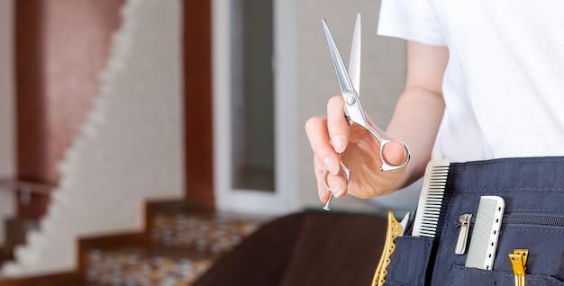 Nożyczki do włosów u fryzjerów ręka w salonie kosmetycznym, wnętrze salonu fryzjerskiego. profesjonalne narzędzia fryzjerskie.