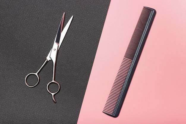 Nożyczki fryzjerskie i grzebienie na czarno-różowym, widok z góry