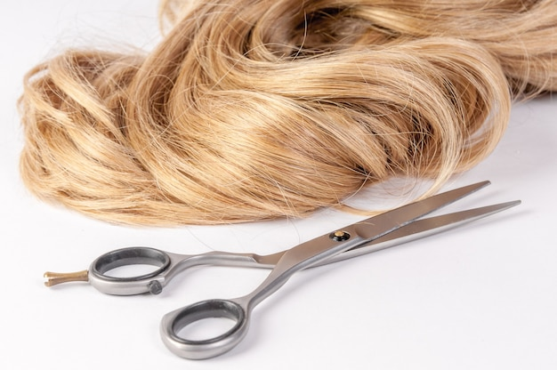 Nożyczki fryzjerskie z pasmem blond włosów na białym