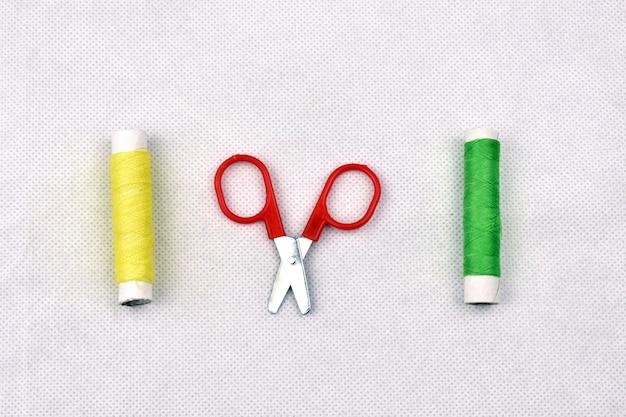 Nożyczki i nici na białym tle