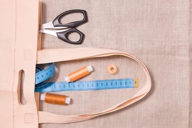 Nożyczki, miarka i kilka szpulek nici w ekologicznej torbie na lnie