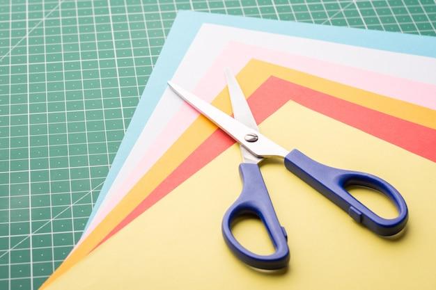 Nożyczki na stosie różnych kolorowych papierów