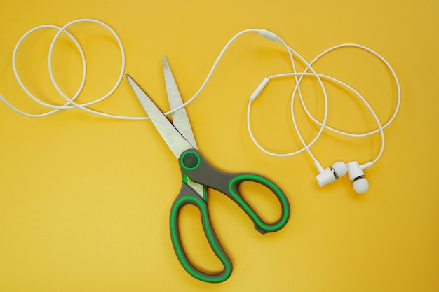 Nożyczki przecinają słuchawki lub przewód słuchawek, aby rozłączyć komunikację na żółtym tle