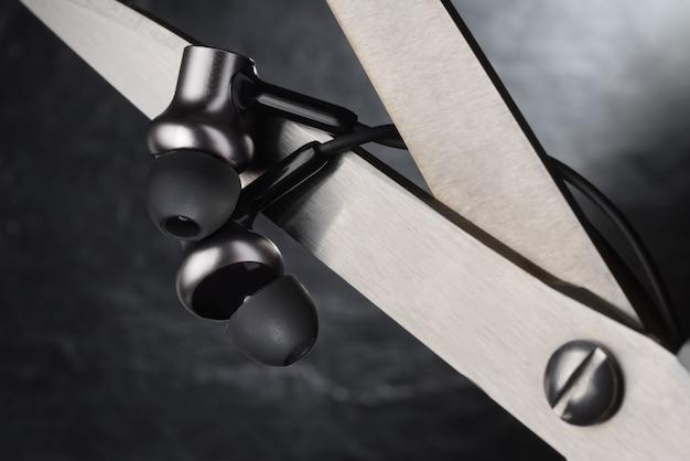 Nożyczki przecinające drut na wkładkach dousznych. prawdziwa koncepcja bezprzewodowych słuchawek stereo tws