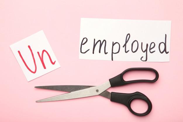 Nożyczki z napisem bezrobotny na różowej powierzchni