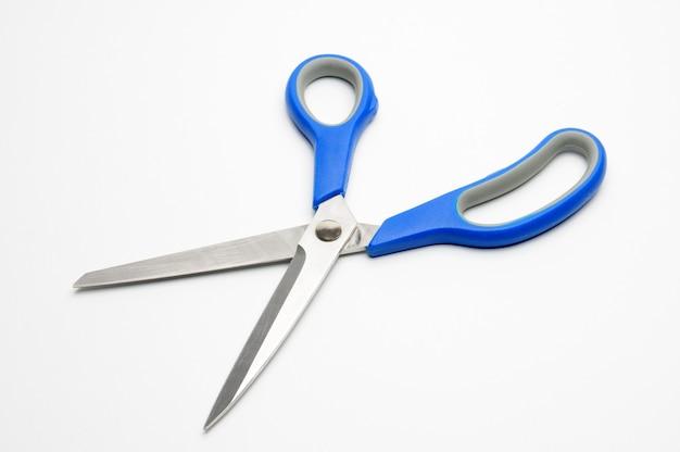 Nożyczki z niebieskim uchwytem dla krawców na białym tle