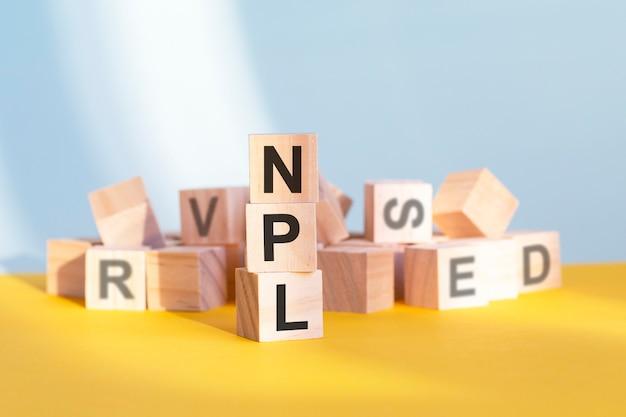 Npl - non performing loans - słowo na drewnianych kostkach. koncepcja biznesu i finansów.