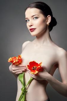 Nude naga dziewczyna z kwiatami tulipanów w dłoni i idealną skórą, seksowna naga brunetka na szarym tle. pielęgnacja skóry twarzy i dłoni latem. jasny naturalny makijaż