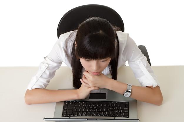 Nudna biznesowa kobieta pracuje i szuka ekran w laptopie.
