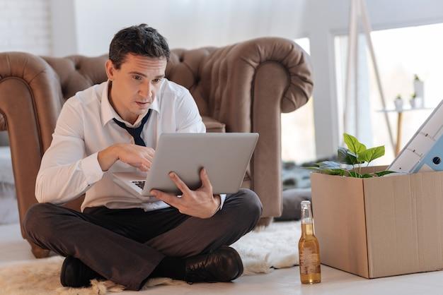 Nudna praca. zmęczony, znudzony młody człowiek siedzi na podłodze ze skrzyżowanymi nogami i patrzy na ekran swojego laptopa, podczas gdy butelka piwa i pudełko z różnymi przedmiotami stoją obok niego