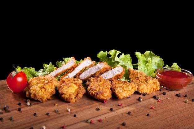 Nuggets z kurczaka, na drewnianym stole z sosem i sałatą na czarnym tle.