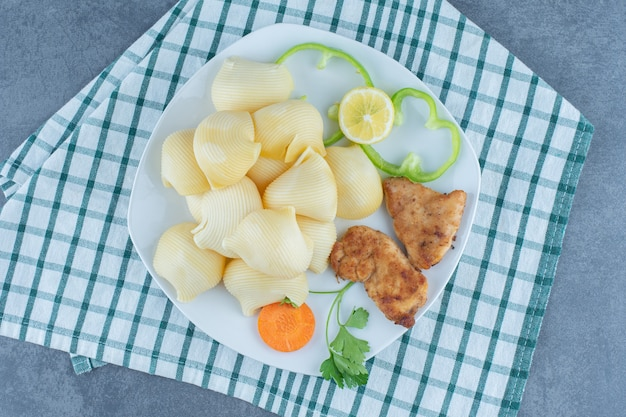 Nuggetsy z kurczaka i gotowany makaron na białym talerzu.