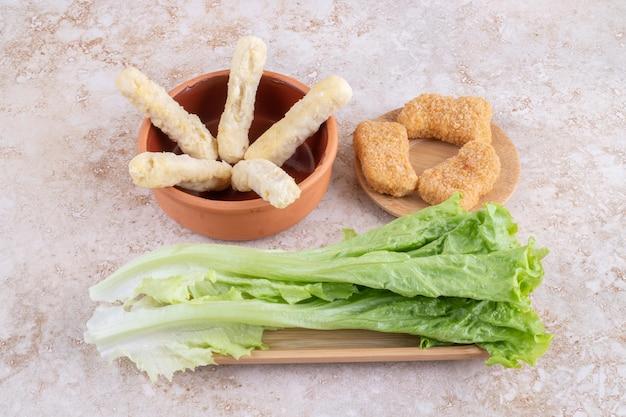 Nuggetsy z kurczaka i paluszki serowe podawane z sałatą.