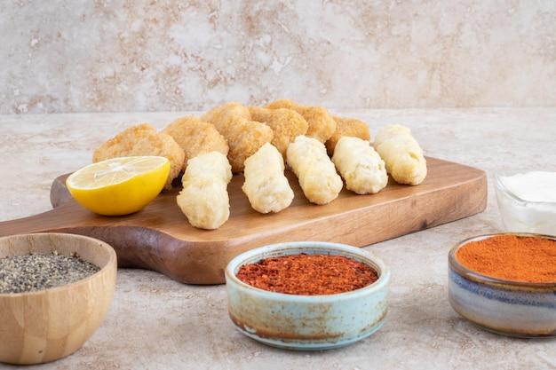 Nuggetsy z kurczaka i paluszki serowe z przyprawami na bok.