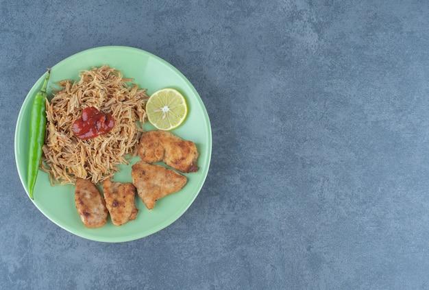 Nuggetsy z kurczaka i smażony makaron na zielonym talerzu.
