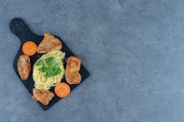 Nuggetsy z kurczaka i spaghetti na czarnej tablicy.