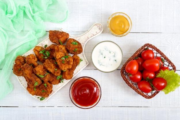 Nuggetsy z kurczaka. kawałki głęboko smażonego chrupiącego mięsa na papierze z różnymi sosami na białym drewnianym stole. tradycyjna przekąska