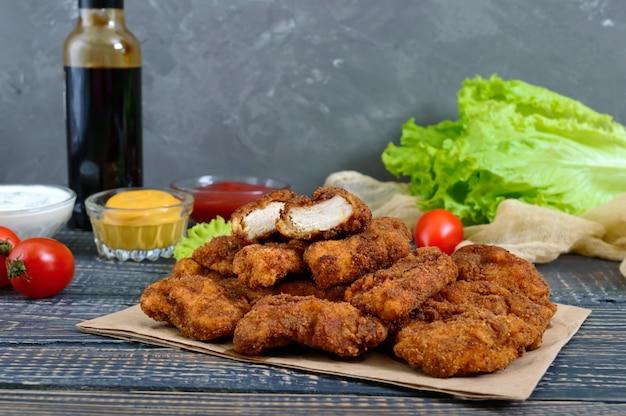 Nuggetsy z kurczaka. kawałki głęboko smażonego chrupiącego mięsa na papierze z różnymi sosami na drewnianym stole. tradycyjna przekąska