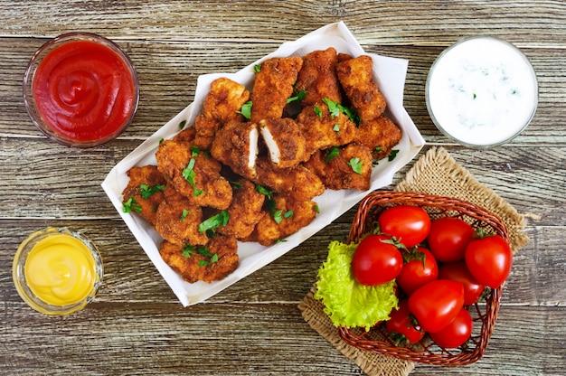 Nuggetsy z kurczaka. kawałki głęboko smażonego chrupiącego mięsa z różnymi sosami na drewnianym stole. tradycyjna przekąska