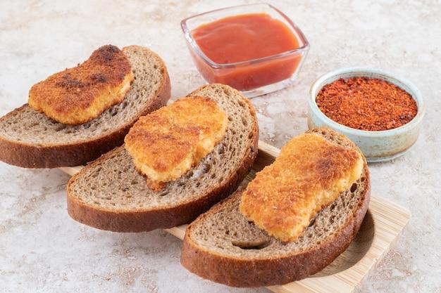 Nuggetsy z kurczaka na drewnianej desce z sosami na bok.