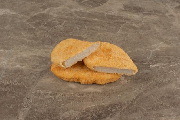 Nuggetsy z kurczaka na marmurowej powierzchni.
